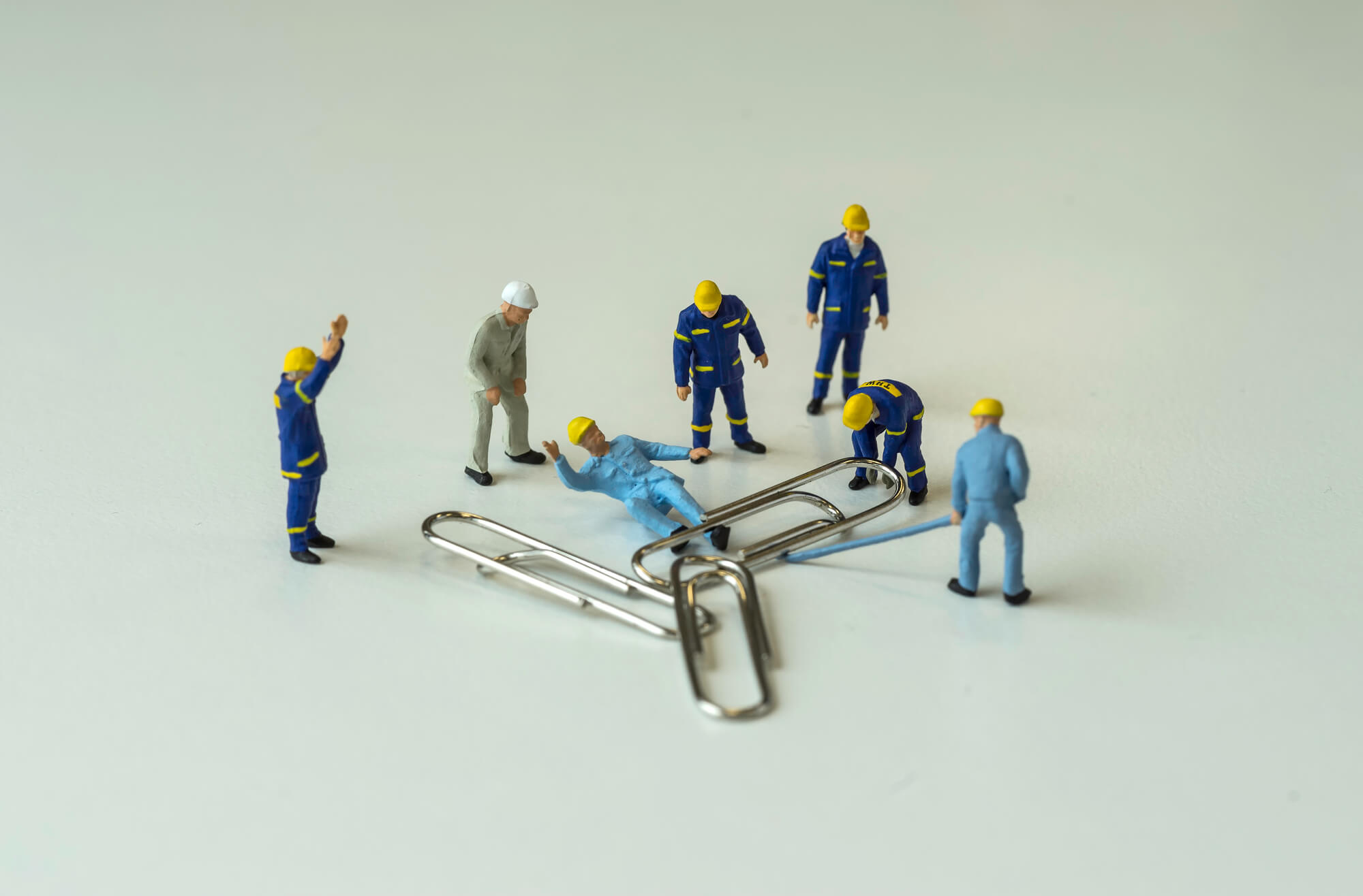 mini worker trapped under fallen paperclip