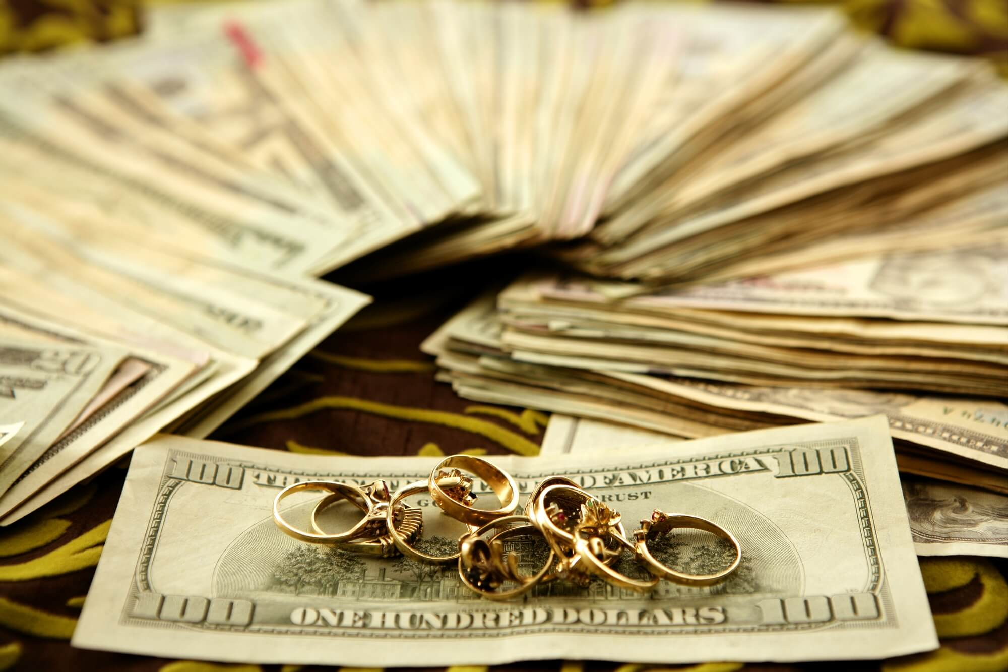 pile of rings on stack of cash