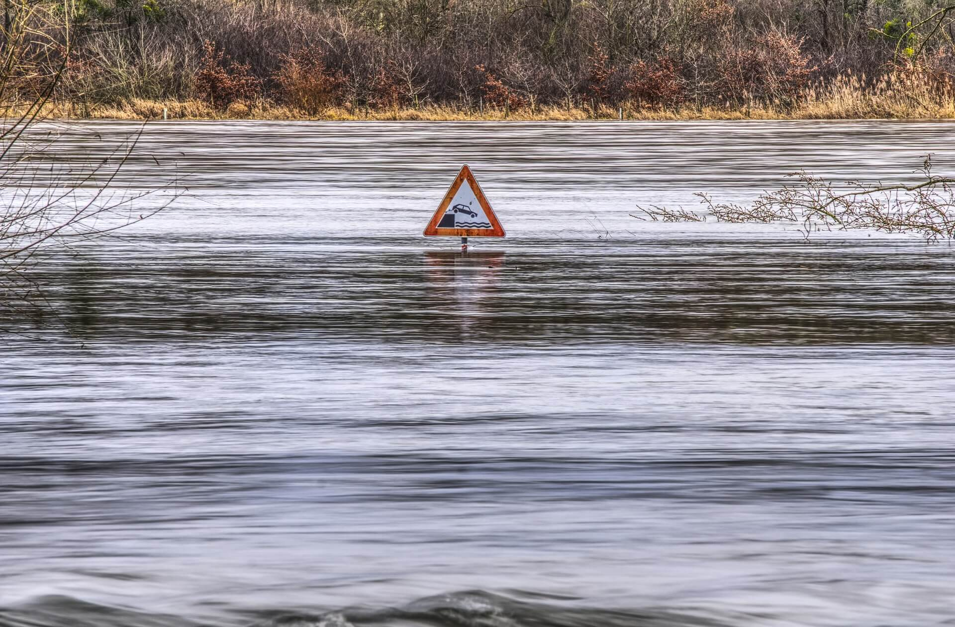street sign nearly submerged with floodwaters