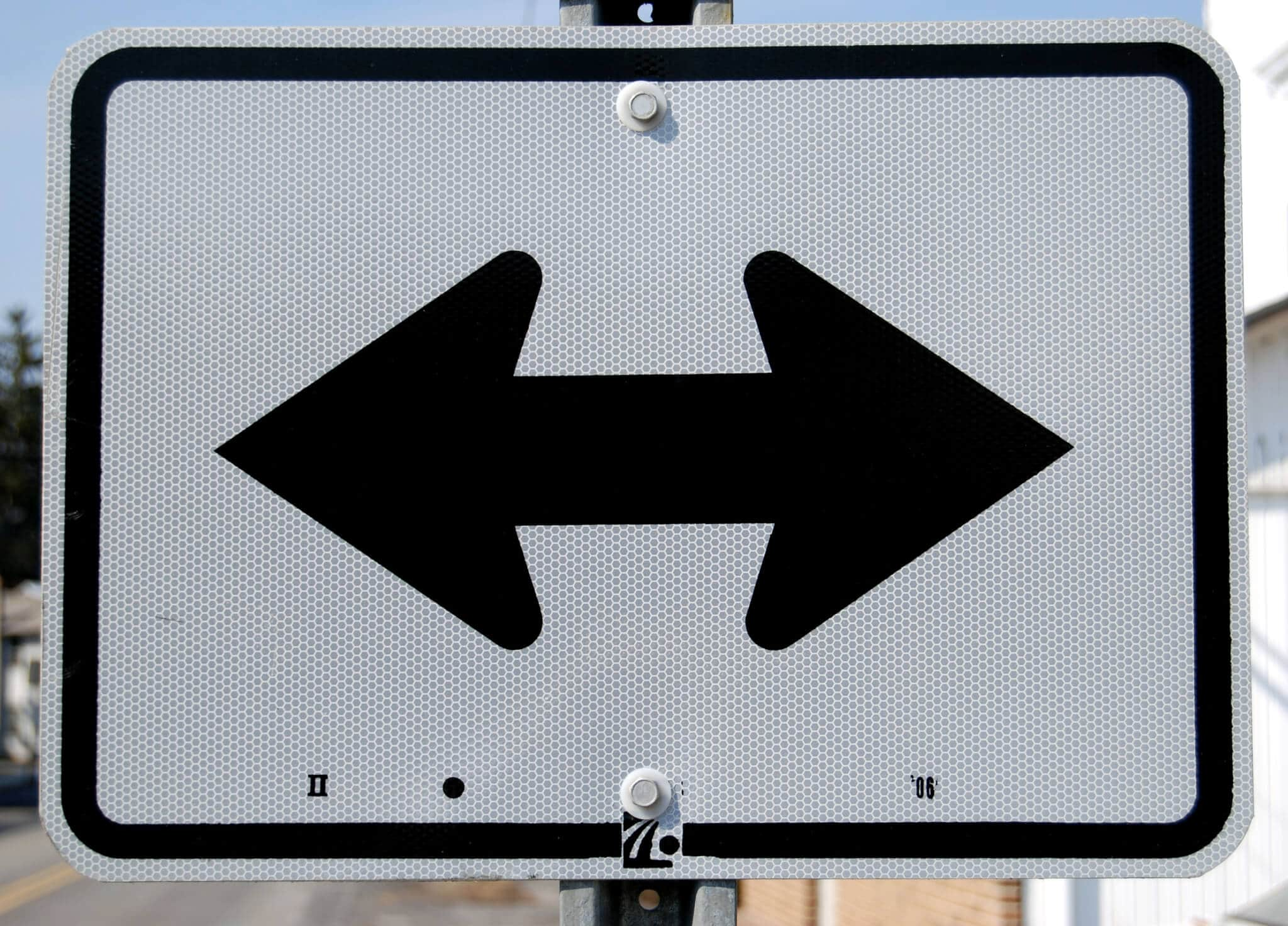 street sign with arrows pointing right and left
