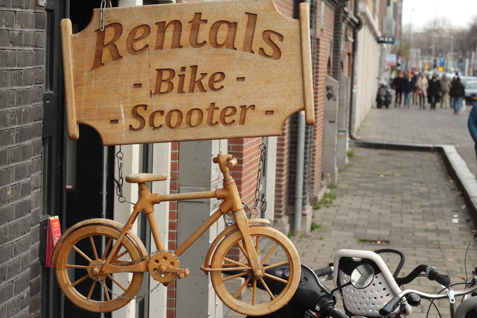 wooden storefront sign advertising bike and scooter rentals
