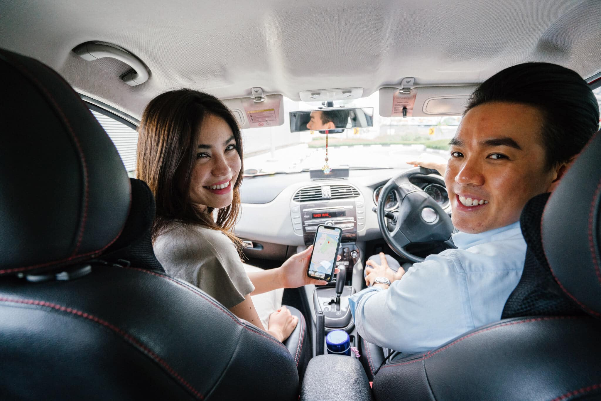 man and woman smiling in front car seats