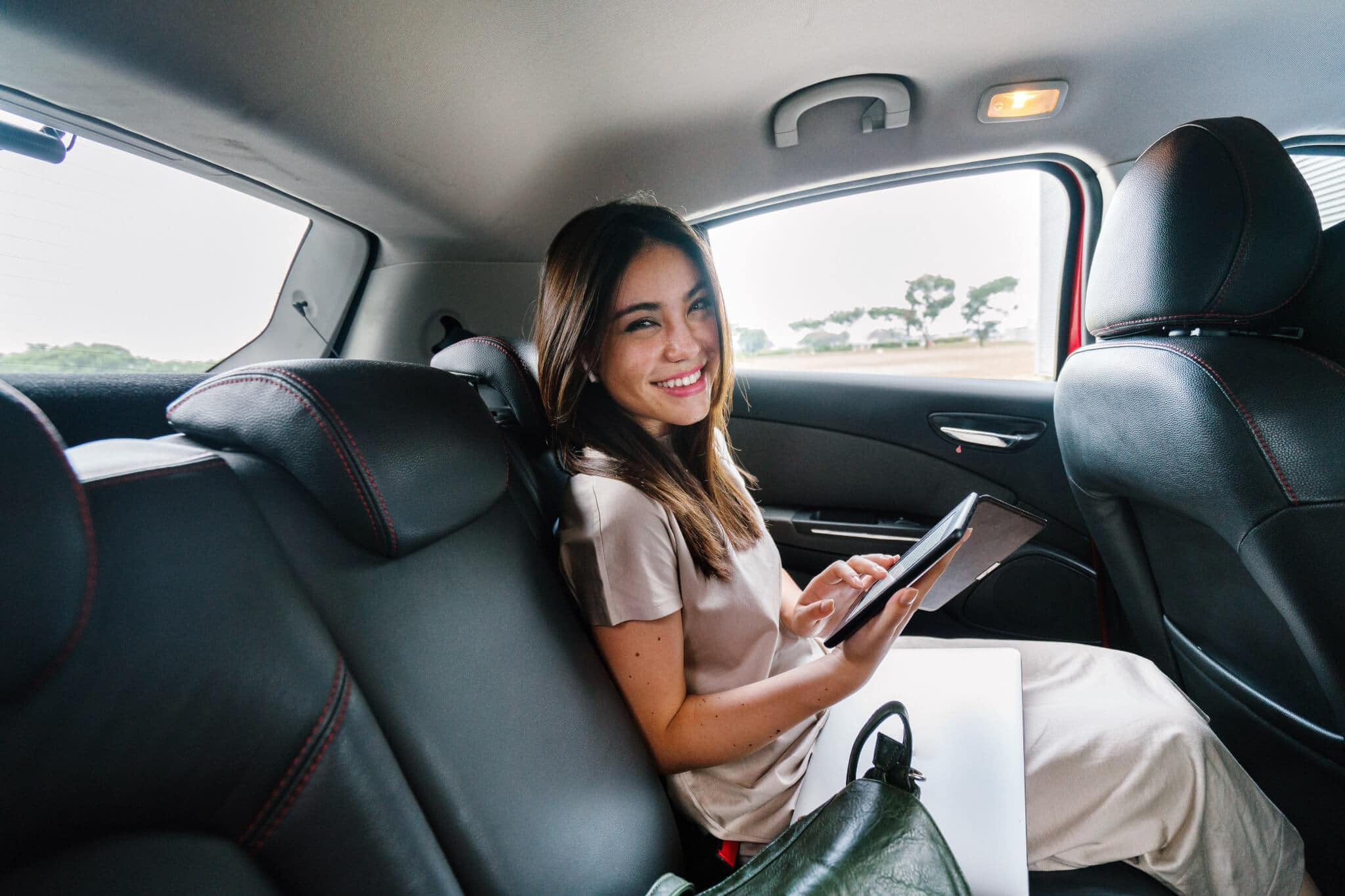 smiling businesswoman working in backseat