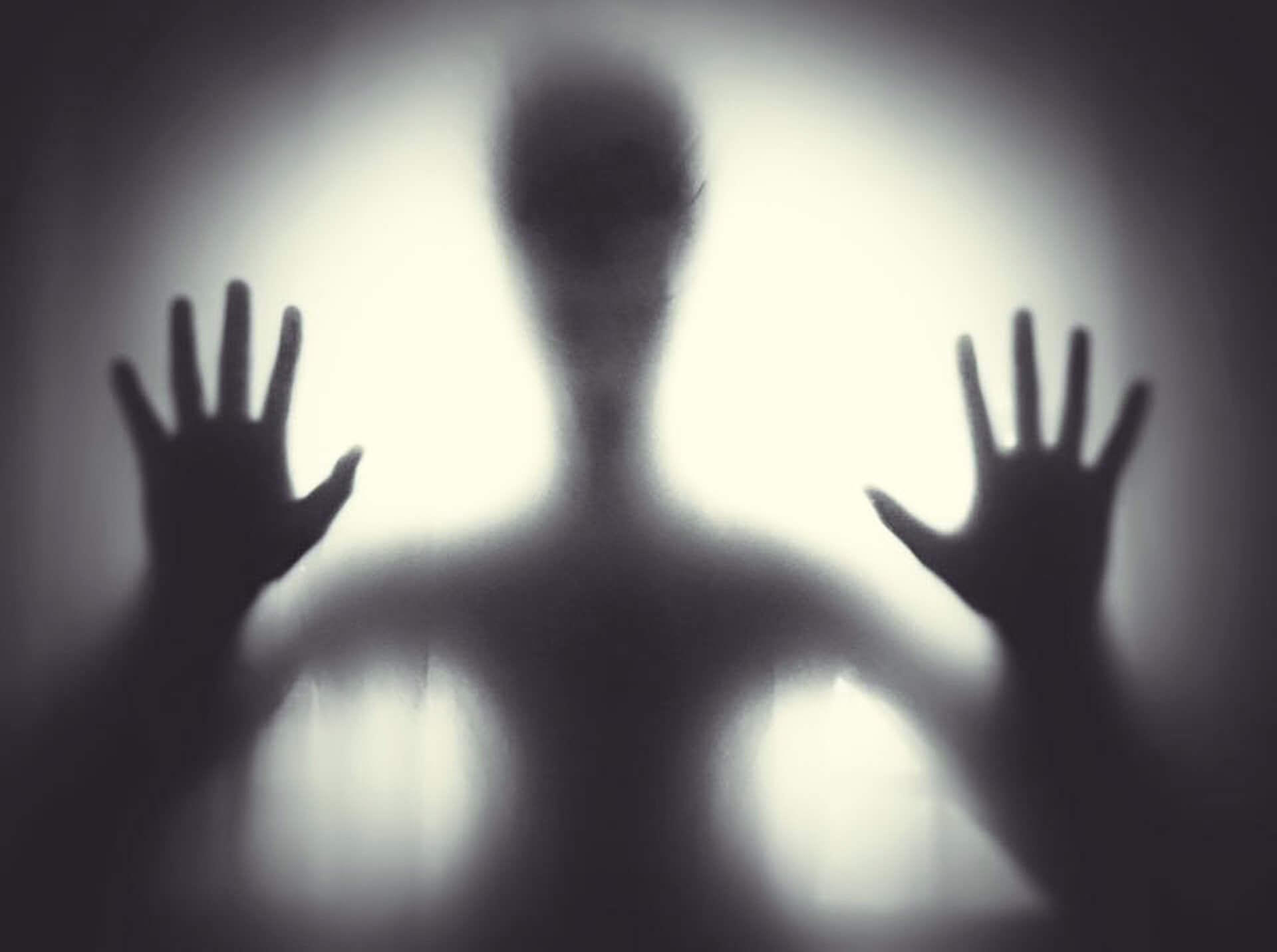 ghostly alien silhouette seen through glass