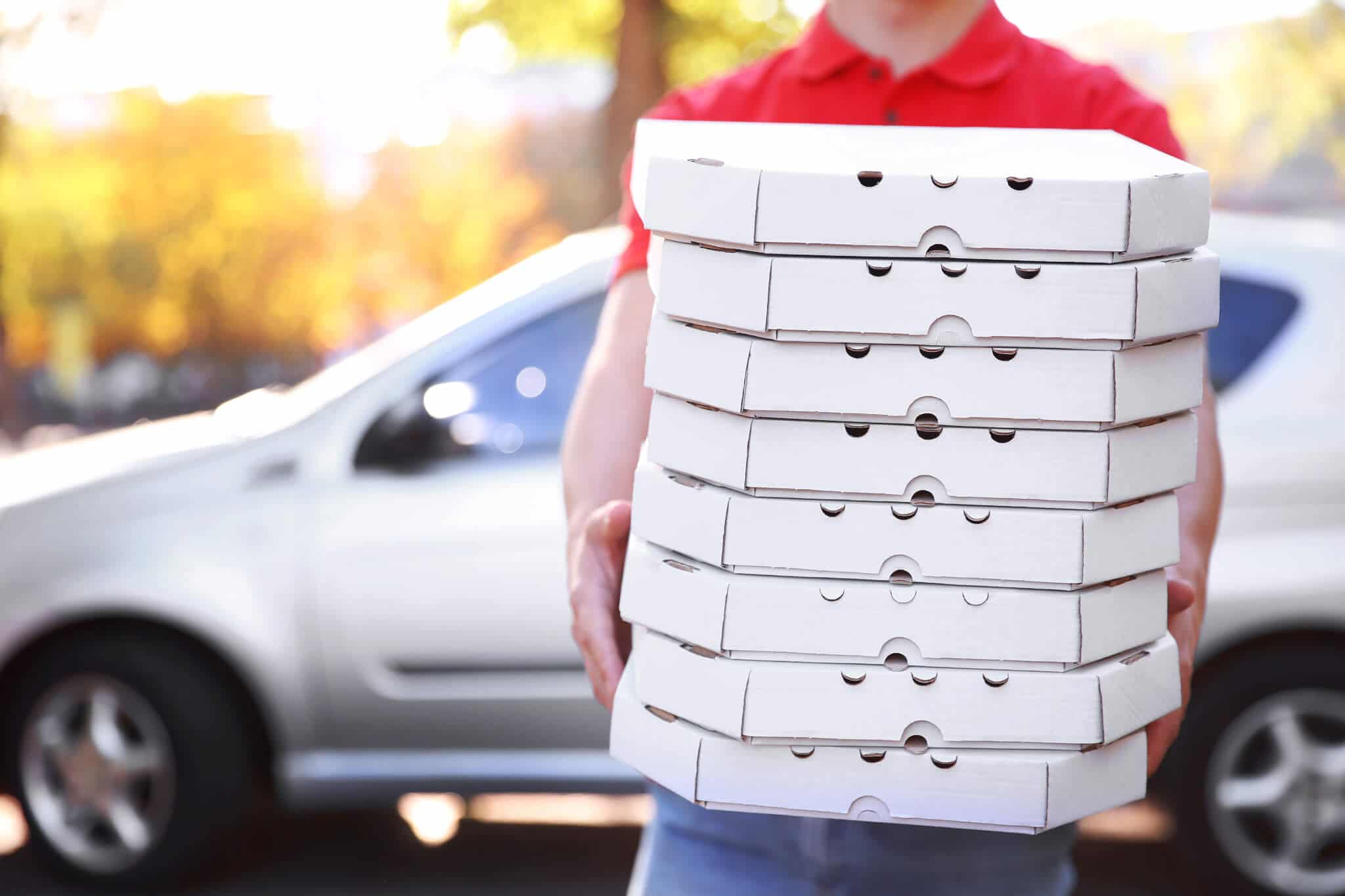 young man in front of car holding stack of pizza boxes