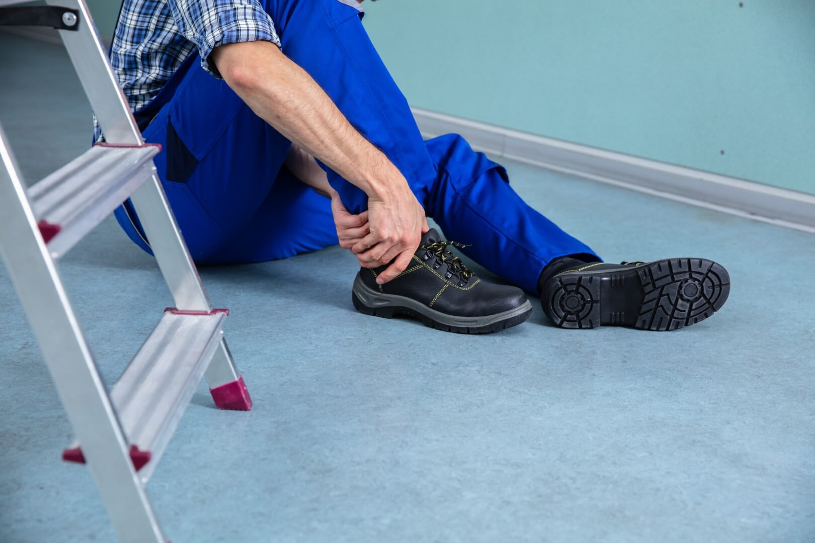 handman clutching ankle after falling from ladder