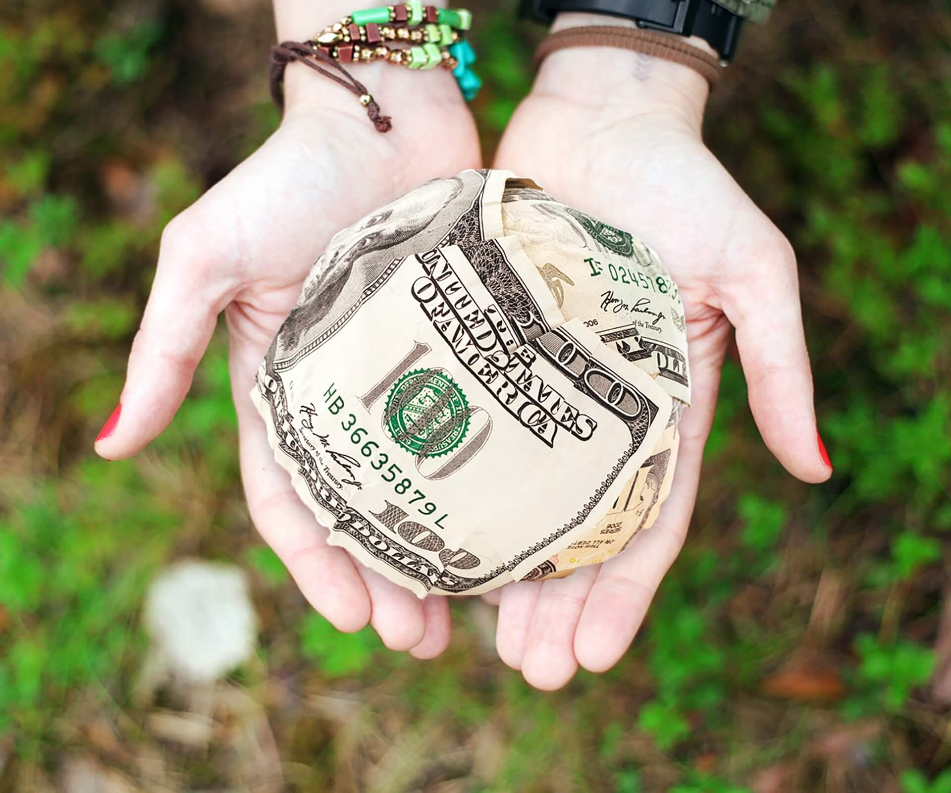 hands holding ball of cash