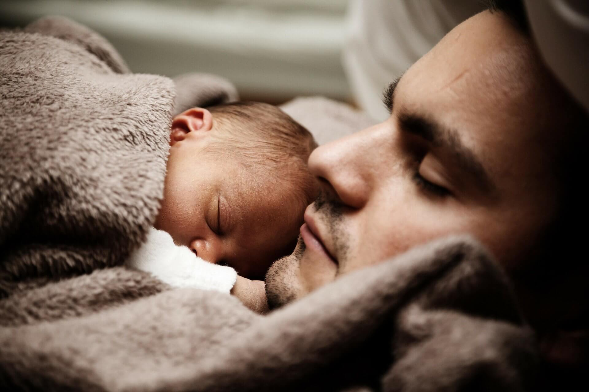 dad and sleeping baby on chest