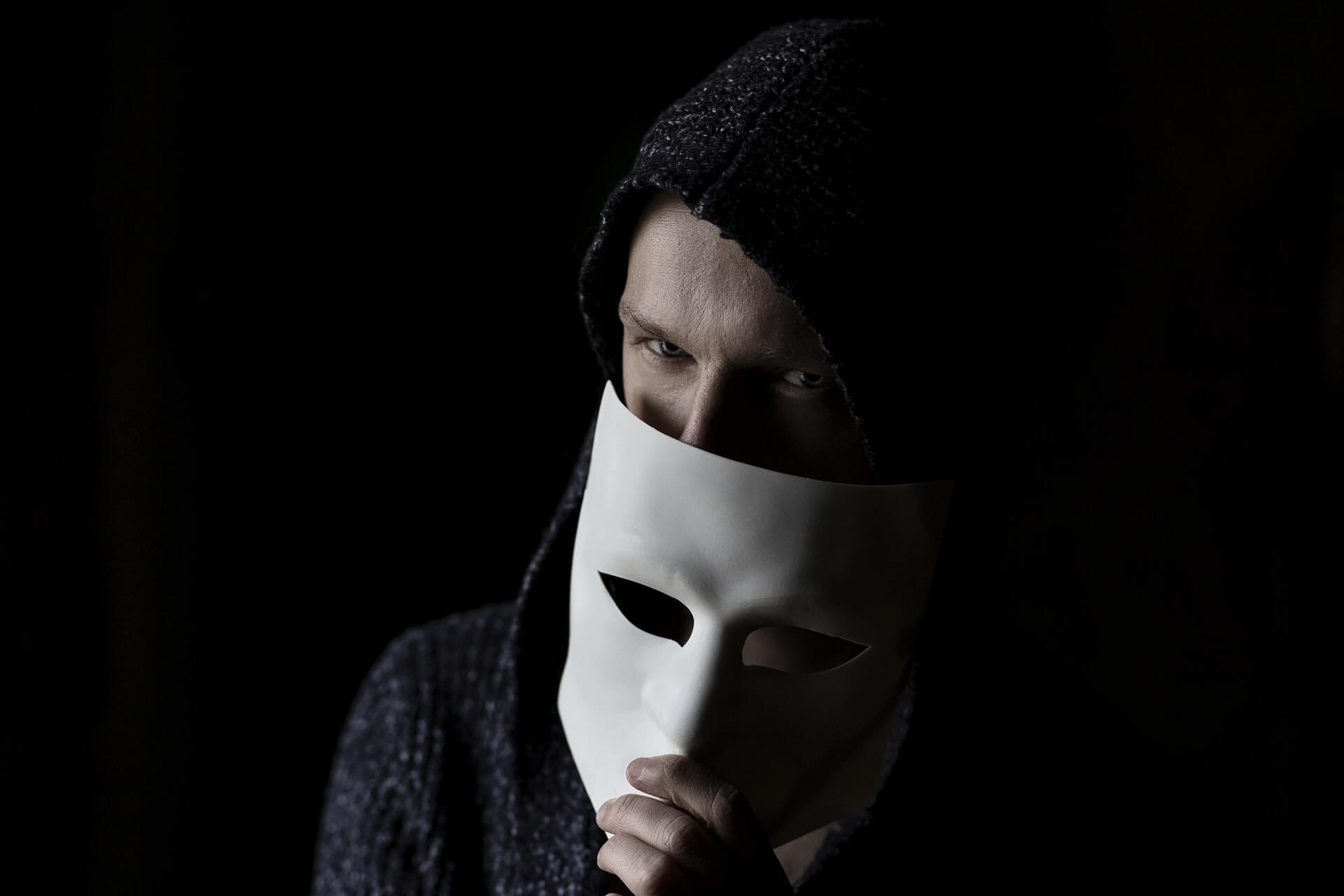 Man peeking out from behind mask