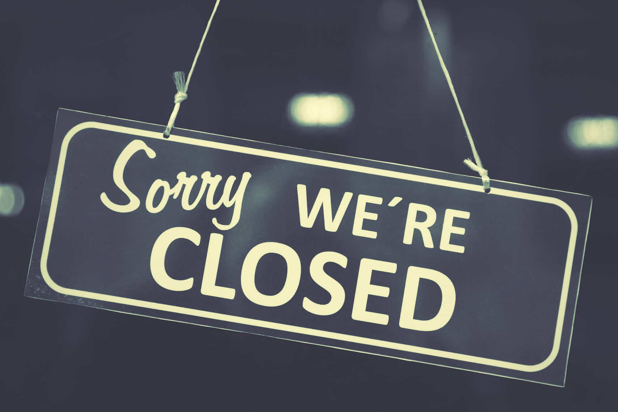 """Sorry We're Closed"" sign in business door"