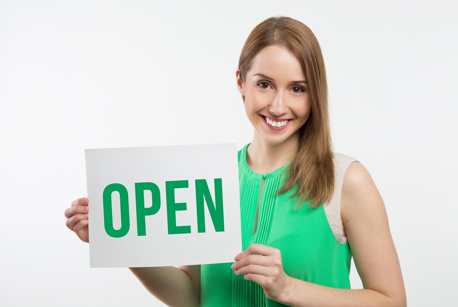 "Women holding ""Open"" sign"