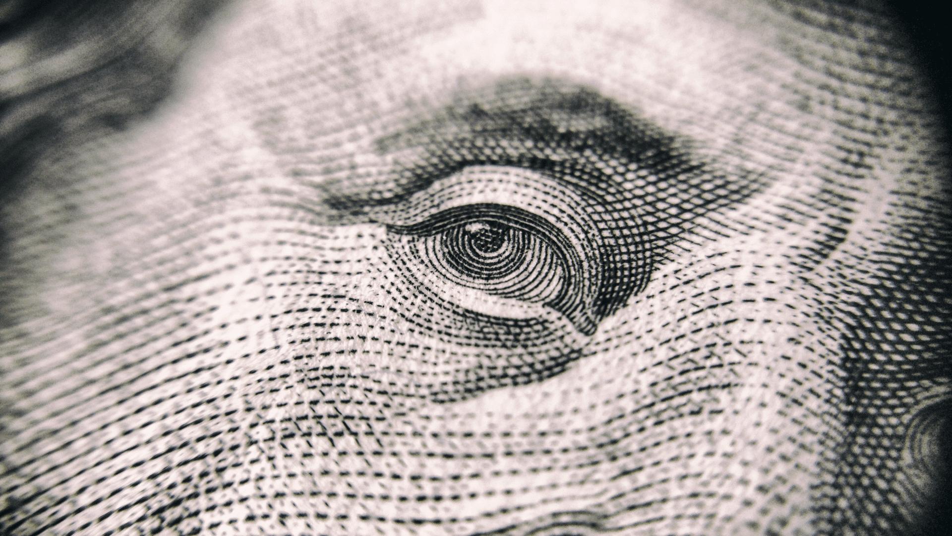 close up of Benjamin Franklin's eye on hundred dollar bill