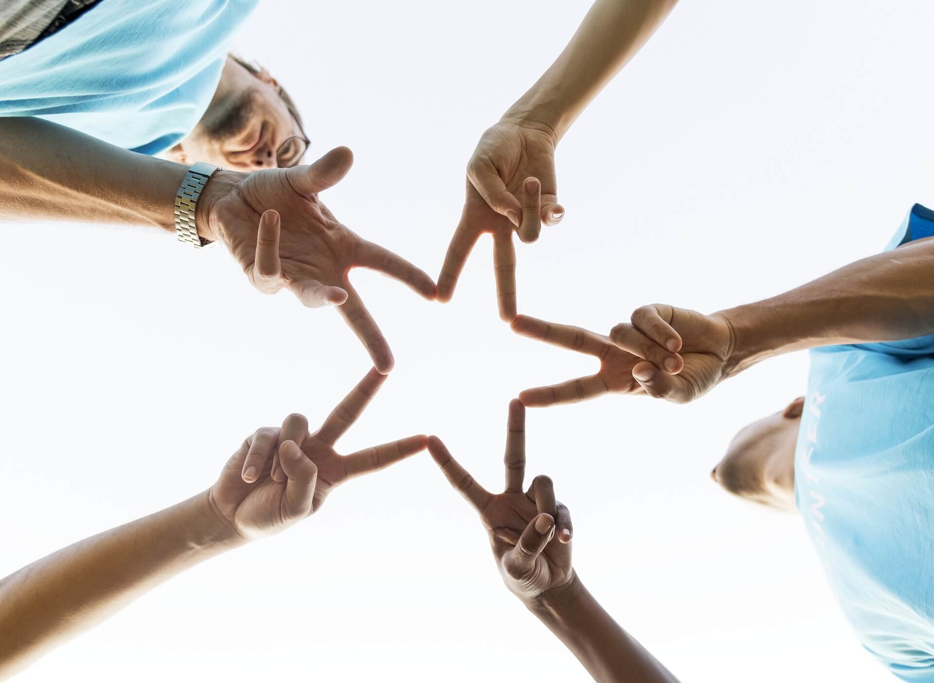 people putting hands together in a star shape